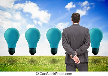 Businessman standing with hands behind back looking at blue light