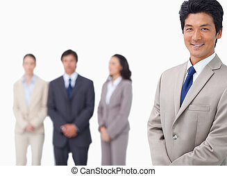 Businessman standing with his colleagues behind him