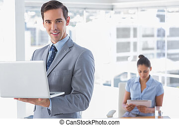 Businessman standing with laptop and smiling at camera