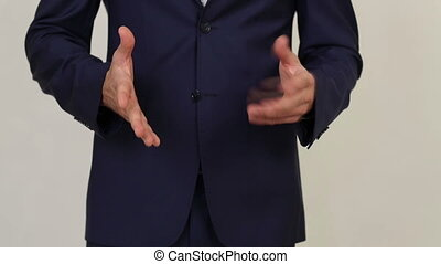 Businessman stands and gesticulation by hands.