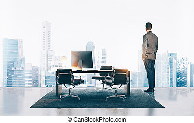 Businessman stands in contemporary office and looking at the city. Horizontal