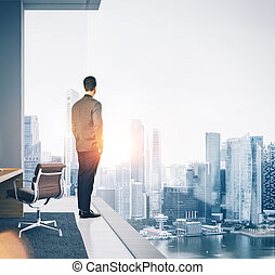 Businessman stands in contemporary office and looking at the city. Square