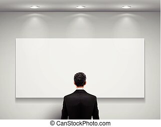 businessman stands in front of blank board