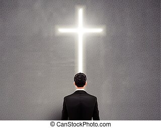 businessman stands in front of the cross light