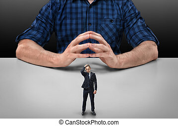 Businessman stands touching his head with hand in front of cropped portrait big man sitting