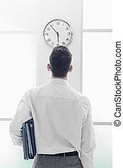 Businessman staring at the clock
