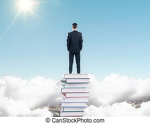 Businessman staying on the stack of books among clouds at blue sky background