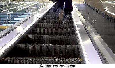 Businessman stepping down from an automatic escalator