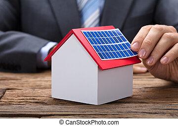 Businessman Sticking Solar Panel On Model Home