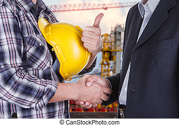 businessman shake hands with engineeringin construction site