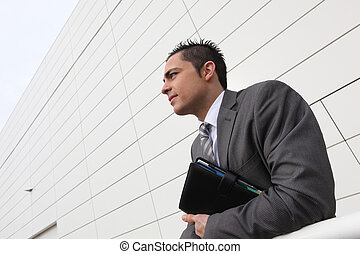 Businessman stood outside building holding diary