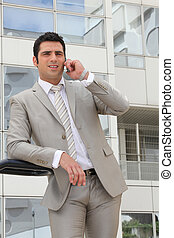 Businessman stood outside office with mobile telephone