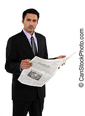 Businessman stood reading the daily newspaper