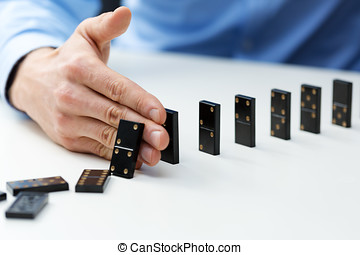 businessman stopping domino effect - business problem solving concept