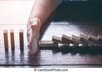 Businessman stopping domino effect with his finger. Business crisis concept.