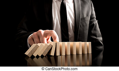 Businessman Stopping the Domino Effect from Small Wooden...