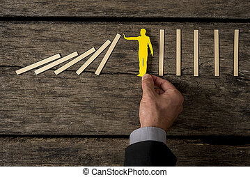 Businessman stopping the domino effect with paper cutout silhouette