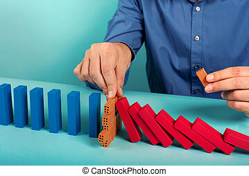 Businessman stops a chain fall like domino game. Concept of preventing crisis and failure in business.
