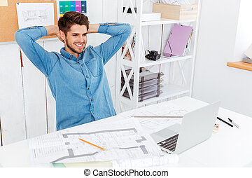 Businessman stretching hands at his workplace in office