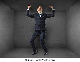 Businessman striving to escape from a small room