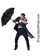 Businessman struggling with umbrella