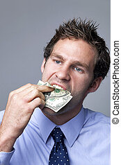 Businessman stuffing money in his mouth.