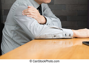 Businessman suffering from pain in the shoulder