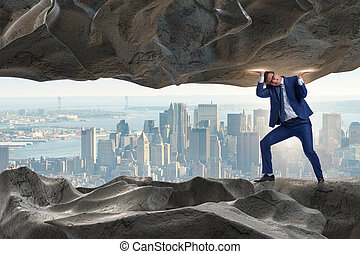 Businessman supporting stone under pressure