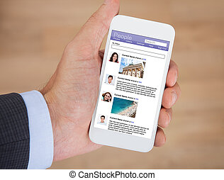 Businessman Surfing Social Networking Site On Smartphone