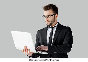 Businessman surfing the net. Cheerful young man in formalwear and glasses working on laptop while standing against grey background