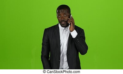 Businessman takes the phone and starts talking on the phone. Green screen