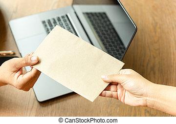 Businessman taking bribe money in brown envelope from partner.