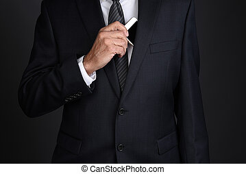 Businessman taking his smart phone from his inside suit jacket pocket