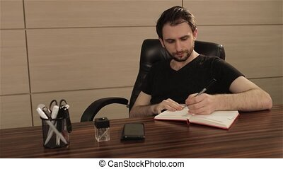 Businessman taking notes with laptop background. Businessman writing in a notebook at a table. Business concept