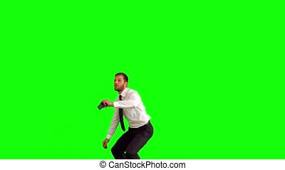 Businessman taking self portrait while leaping on green...