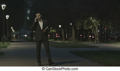 Businessman talking by phone while walking in park and use organizer.
