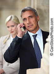 Businessman talking on cellphone outdoors