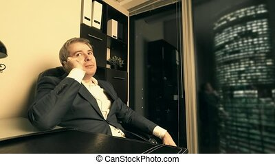 Businessman talking on his cell phone in the office in downtown in the evening