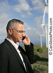 Businessman talking on his mobile phone in a wind turbine park