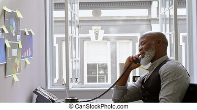 Businessman talking on landline at desk 4k