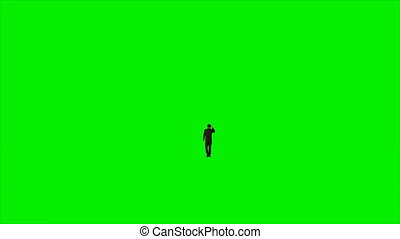 Businessman talking on mobile phone against green screen,...