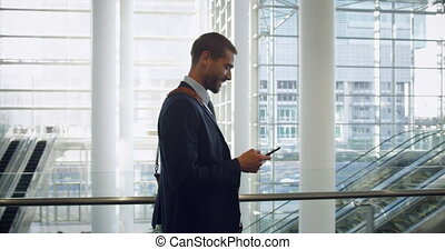 Businessman talking on mobile phone in the lobby at office 4k
