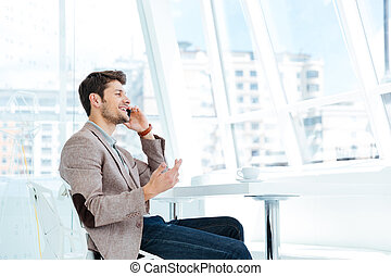 Businessman talking on mobile phone while sitting at the table