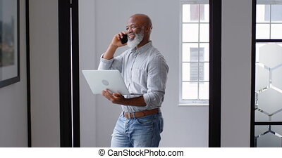 Businessman talking on mobile phone while using laptop 4k