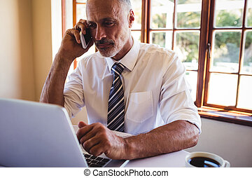 Businessman talking on mobile phone while using laptop