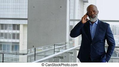Businessman talking on mobile phone while walking 4k -...
