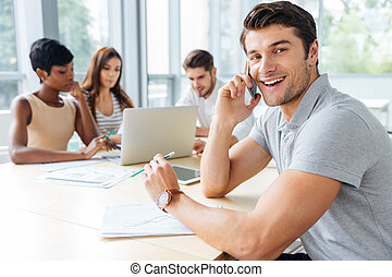 Businessman talking on mobile phone while working with business team