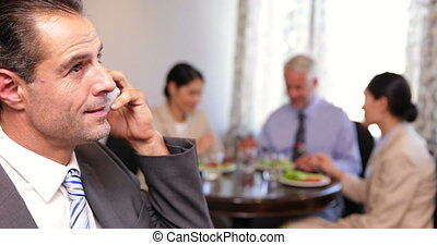 Businessman talking on phone at business lunch at a restaurant