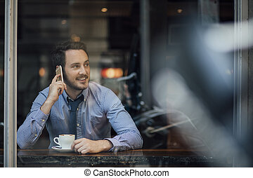 Businessman Talking On Phone In Cafe - Millennial...