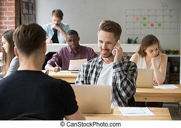 Businessman talking on phone in coworking space